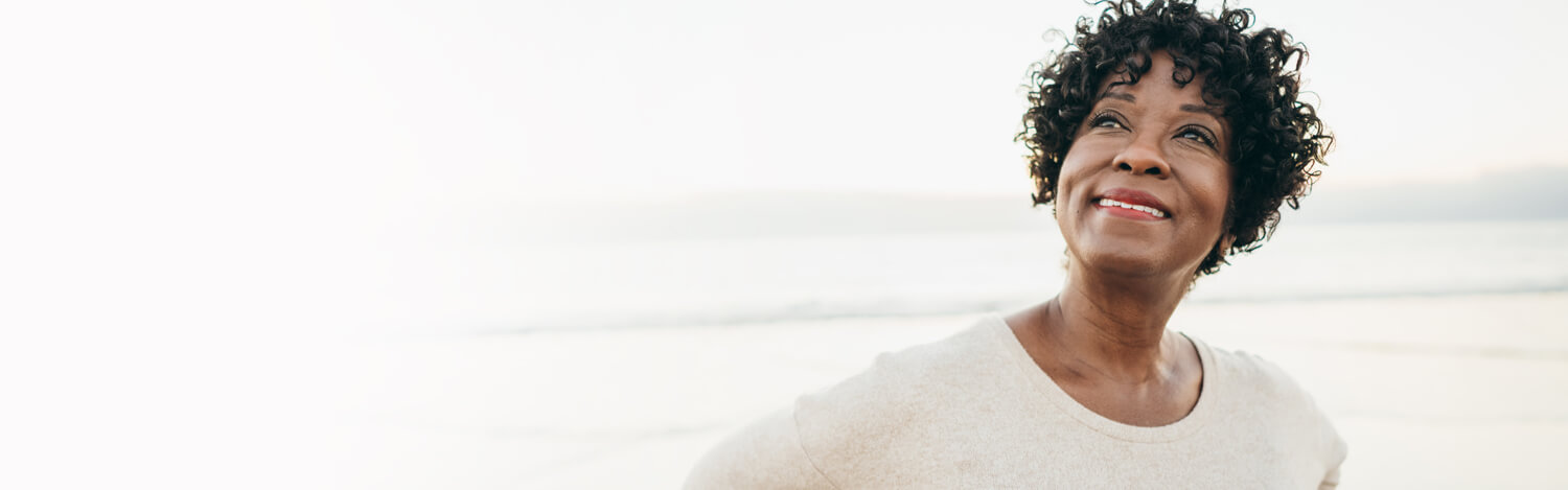 Smiling woman outdoors on beach contemplating retirement