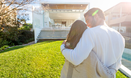 Couple who are new vacation rental owners look at their purchase and embrace.