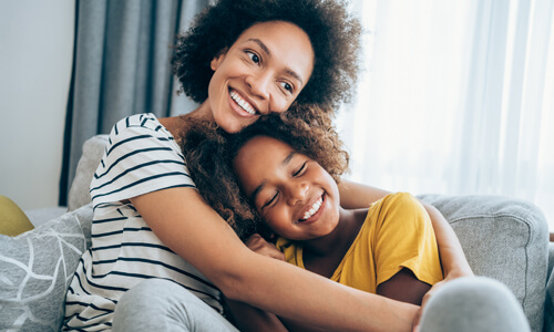 Mother and daughter embrace on couch, smiling.