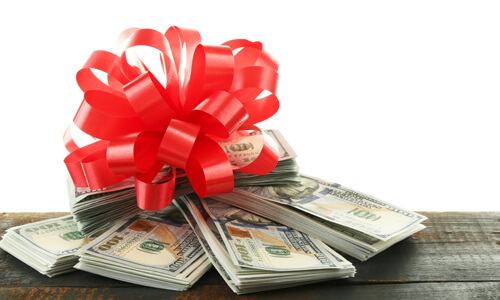 Bundles of cash with a holiday bow on top.
