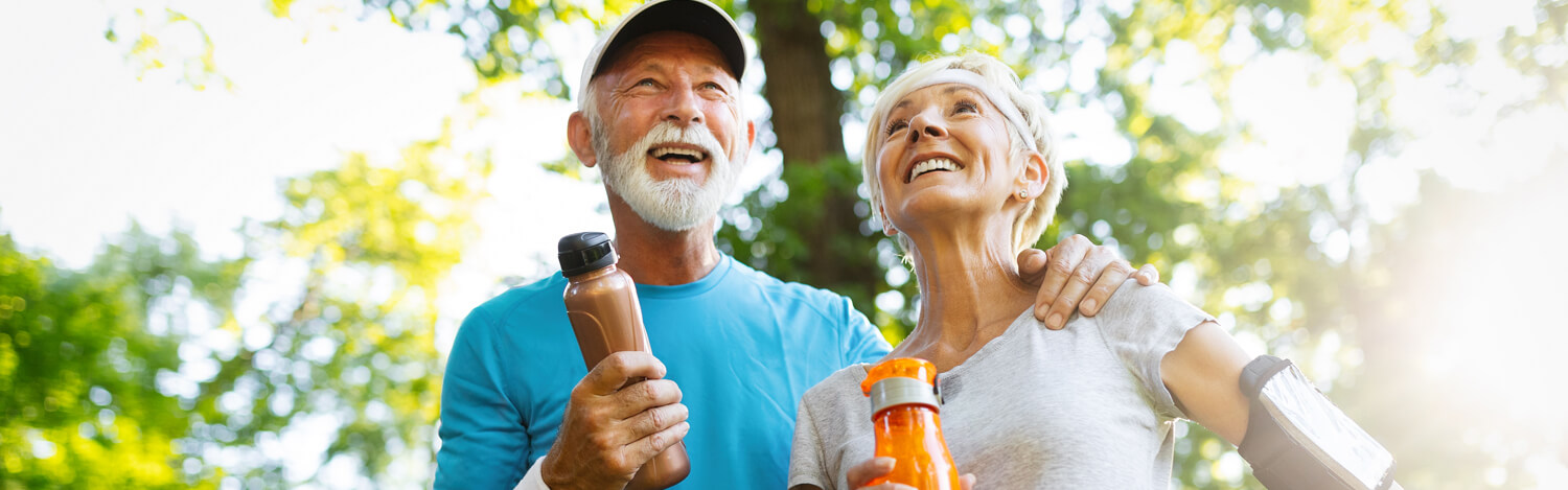 Elderly couple on a healthy walk carrying water bottles, smiling.