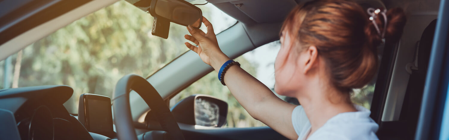 Young woman practicing defensive driving and adjusting her rearview mirror.